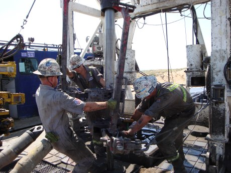 Roughnecks on a drilling rig in Greely, CO use metal tongs weighing hundreds of pounds to make connections between 30' sections of drill pipe.